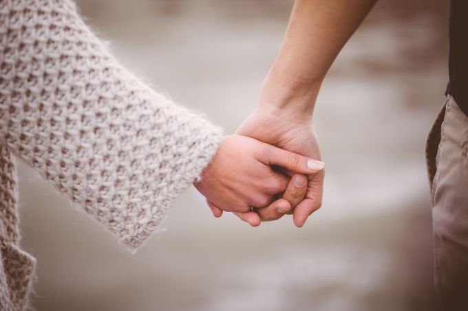 Romantic-couple-tenderly-holding-hands-outdoors-656189652_3869x2579-compressor