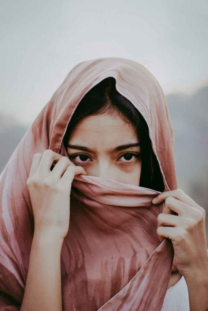 portrait photo of woman covering her mouth with brown scarf